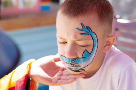 Boy painting face with shark outdoors.