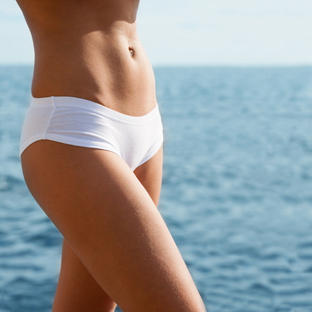 Young woman with a slender figure in panties on a sea background. photo