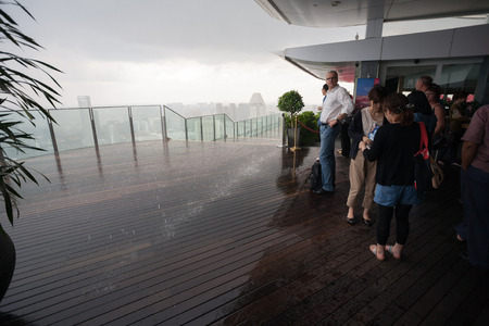 differs: SINGAPORE - NOVEMBER 06, 2012: Tourists on the observation deck of a skyscraper in the rain in Singapore. Weather in Singapore differs monsoon tropical climate, so here comes the big monthly rainfall Editorial