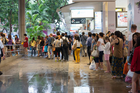 SINGAPORE - NOVEMBER 09, 2012: People queue for a taxi street Orchard Road in Singapore.Orchard Road - this 2.2 km street is the retail and entertainment hubs of Singapore and major tourist attraction