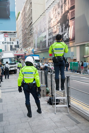 HONG KONG - NOVEMBER 14, 2012: Police men on the Queens Road. Hong Kong has a unified police force - Hong Kong Police Force, it is considered one of the top notch organizations in world.