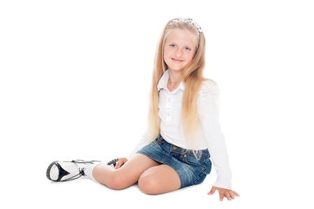 6 years girl: Portrait of sitting blond girl in denim skirt isolated on white.