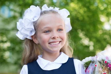 grader: Joyful girl first grader with flowers.