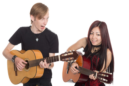 Singing musicians with guitars. Interracial young couple, Asian woman and Caucasian man. photo