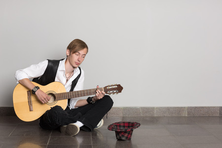 busker: Street musician playing his guitar.  Stock Photo