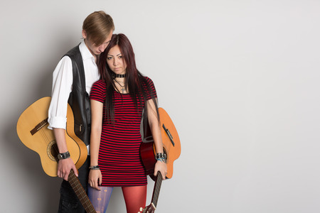 Young musicians with guitars at the gray wall. Interracial young couple, Asian woman and Caucasian man. photo