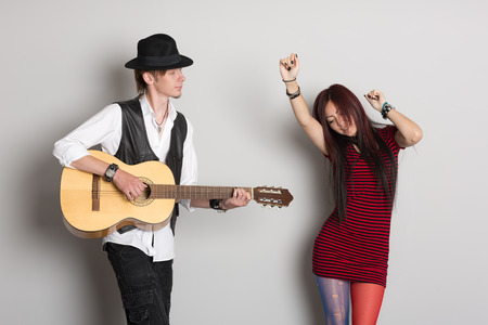 Buskers play the guitar and dance. Asian woman and Caucasian man.  photo