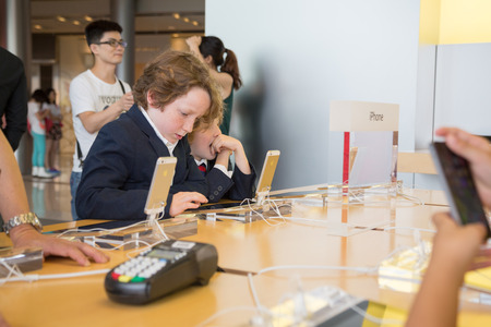 HONG KONG, CHINA - JUNE 15, 2014: Young visitors at Apple store in Hong Kong. Store is in a shopping center IFC Mall, it is very popular with locals and tourists visiting Hong Kong.