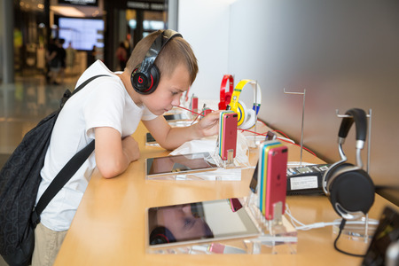 HONG KONG, CHINA - JUNE 18, 2014: The boy with headphones in Apple store in Hong Kong. Store is in a shopping center IFC Mall, it is very popular with locals and tourists visiting Hong Kong.