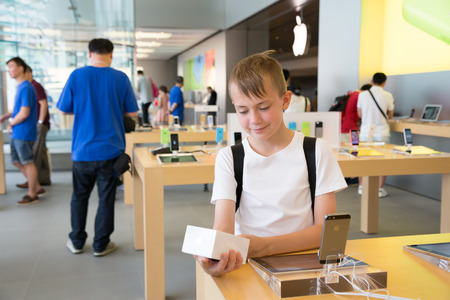 HONG KONG, CHINA - JUNE 18, 2014: Boy looks at the packaging at Apple store in Hong Kong. Store is in a shopping center IFC Mall, it is very popular with locals and tourists visiting Hong Kong.