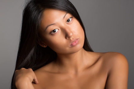 Beautiful young asian woman with bare shoulders. photo