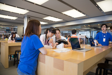 HONG KONG, CHINA - JUNE 15, 2014: Buyers and shop consultants at Apple store in Hong Kong. Store is in a shopping center IFC Mall, it is very popular with locals and tourists visiting Hong Kong.