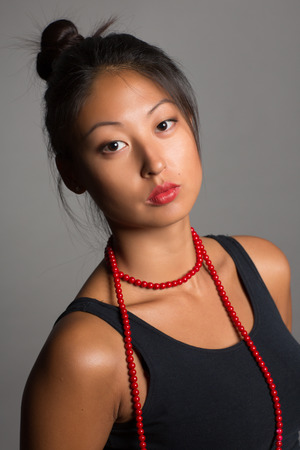 Beautiful Asian  girl with red beads. photo