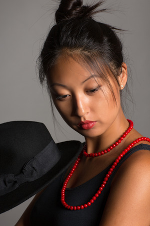 Stylish asian young woman on a gray background. photo