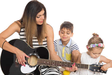 Young mother playing guitar for their children. photo