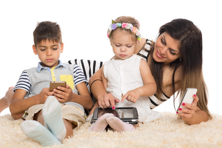 Mom and children with smartphones and tablet pc. photo