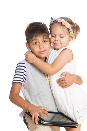 Brother and sister hugging each other. Brother holding tablet PC. photo