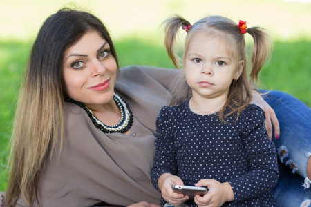 Young mother and her two year old daughter holding a smartphone. photo