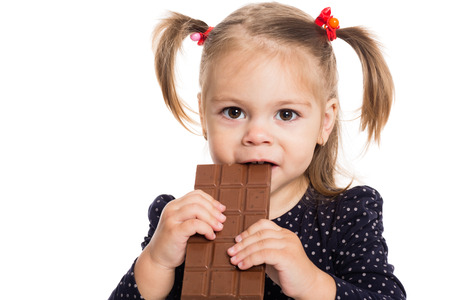 two years: Charming little girl eating chocolate. Two years. Stock Photo