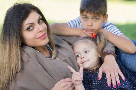Mom with son and daughter lie on the grass in the park. photo