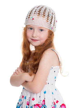 Red haired little girl of six years in a knitted cap isolated on white background. photo
