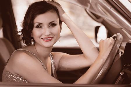 Smiling beautiful brunette woman driving a car.  photo