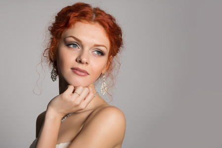 Charming thoughtful bride with red hair looking away. photo
