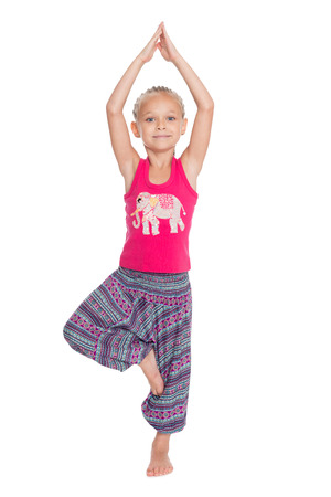 European little girl performs gymnastic exercise in Thai dress photo