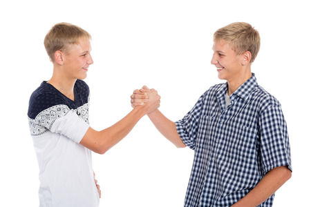 Young twin brothers shake hands, isolated on white photo