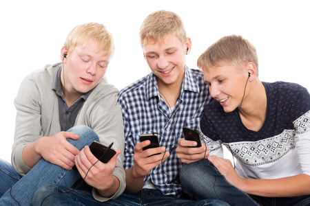 Friends use smartphones sitting on the carpet. Two of the boys twin brothers. photo