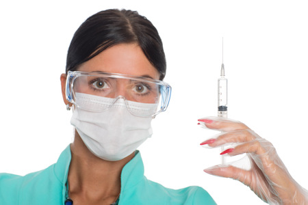 Nurse in a mask with a syringe for injection. Focus on the syringe. photo
