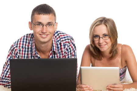 Cheerful young man and woman with a PC isolated on white photo