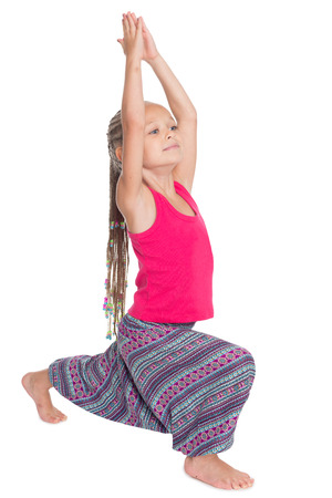 Little girl doing exercises of yoga in Asian attire. Girl is six years old photo