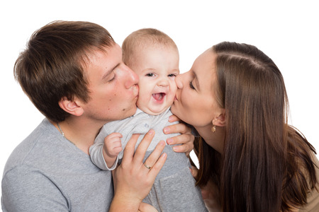 Happy young parents hug and kiss a beloved son photo