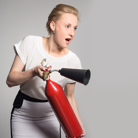An excited young blonde woman with a fire extinguisher photo