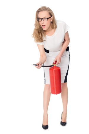 Young scared woman with a fire extinguisher isolated on white photo