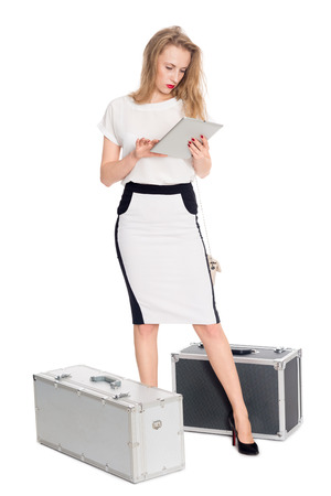 Expecting a pretty girl with a tablet PC and suitcases photo
