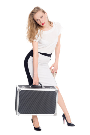 carries: Tired young woman carries a heavy suitcase