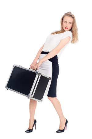 carries: Charming young blonde woman carries a heavy suitcase