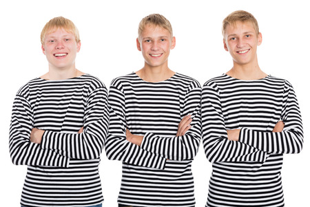 Smiling guys in a striped shirt with arms crossed. Two of the boys twin brothers. photo