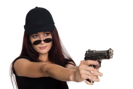 Young woman in a black baseball cap shoots a gun photo