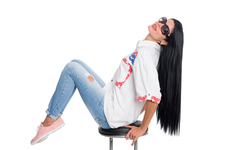 Stylish girl with long black hair in sunglasses sitting on a chair. Girl, twenty-six years. photo