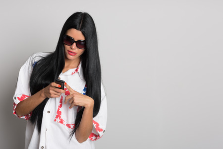 phon: Stylish girl with long black hair uses a cell phone. Girl twenty-six years. Stock Photo