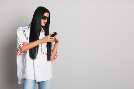 Stylish young woman with long black hair uses a cell phone. Girl twenty-six years. photo