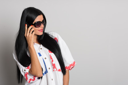 phon: Stylish girl with long black hair talking on a cell phone. Girl, twenty-six years.