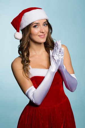Beautiful young woman dressed as Santa Claus on a blue background photo