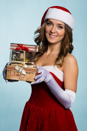 Beautiful young woman dressed as Santa Claus with gifts photo