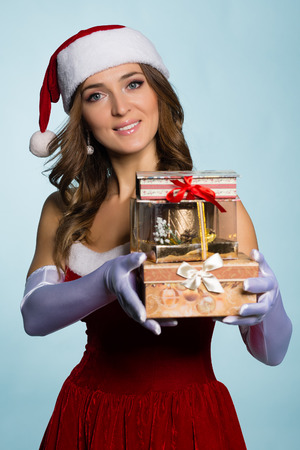 Beautiful young woman in Santa Claus clothes with gifts over blue background photo
