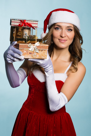 Beautiful young woman in Santa Claus clothes with gifts photo