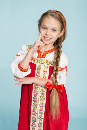 guadaña: Muchacha rubia con una guadaña en el traje popular tradicional ruso. Niña de siete años.